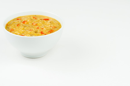 Home made lentil soup in a white bowl on a white table top with copy space Reklamní fotografie