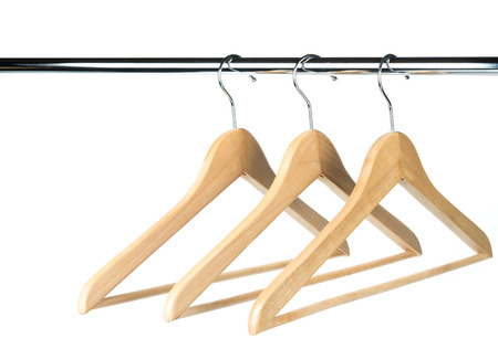 Three empty wooden coat  clothes hangers on a clothes rail with a white background. Potential copy space above and to the left of hangers. Reklamní fotografie