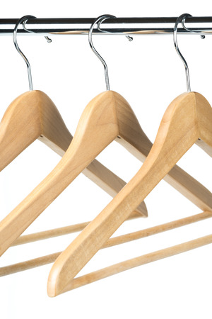 Empty wooden coat  clothes hangers on a clothes rail with a white background