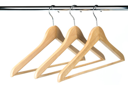 Three wooden coat  clothes hangers on a clothes rail with a white background. Potential copy space to the left of hangers.
