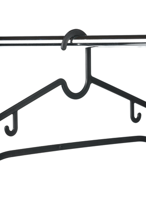 Black pastic clothes hanger on a chrome wardrobe rail with a white background Reklamní fotografie