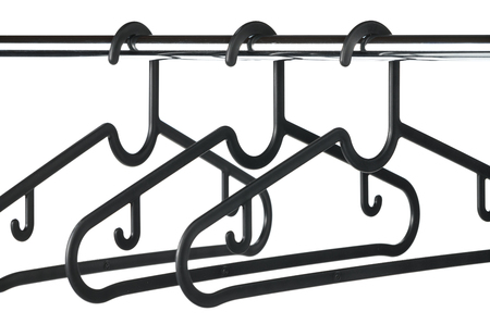 Three empty black coat  clothes hangers on a clothes rail with a white background.