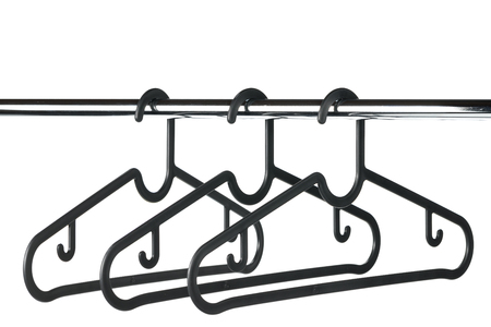 Three empty coat  clothes hangers on a clothes rail against a white background. Copy space above rail.