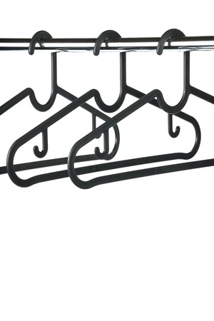 Three black coat  clothes hangers on a clothes rail against a white background. Copy space beneath hangers.