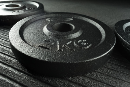 Dumbbell weight plates on a fitness studio  weight training gym floor