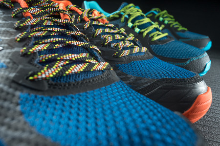 Two pairs of colourful exercise trainers  running shoes inside a gym