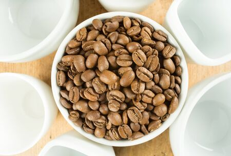 Lightly roasted brown coffee beans surrounded by white cups on a wooden table top