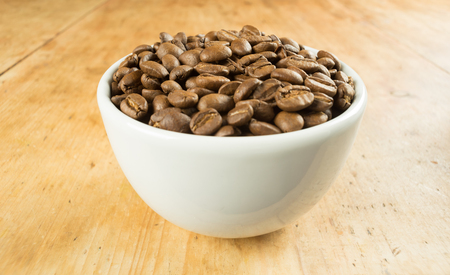 Light roast brown coffee beans in a white bowl on a wooden table top Reklamní fotografie