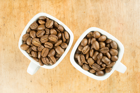 Light roast brown coffee beans in two white coffee cups on a wooden table top Reklamní fotografie
