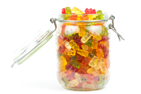 Mixed gummy bears  jelly baby candy sweets in an open jar on a white background