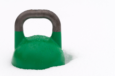 Green weight training kettlebell covered with water droplets outside in the snow. Potential copy space to the right of kettlebell. Green competition kettlebells weigh 24kg.