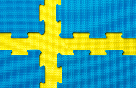 Foam interlocking yellow and blue floor tiles in the shape of the Swedish flag. Potential use as a background with copy space or made in Sweden concept.