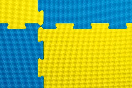 Interlocking blue and yellow foam flooring tiles inside a gym, kindergarten, play room or school classroom. Potential use as a colourful background with copy space. Reklamní fotografie