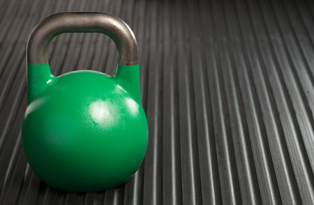 Green 24kg weight lifting kettlebell inside a gym. Copy space to the right of kettlebell. Reklamní fotografie
