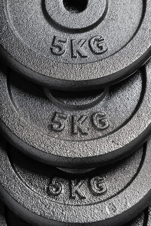 Stack of 5kg barbell  dumbbell weight plates inside a weightlifting gym