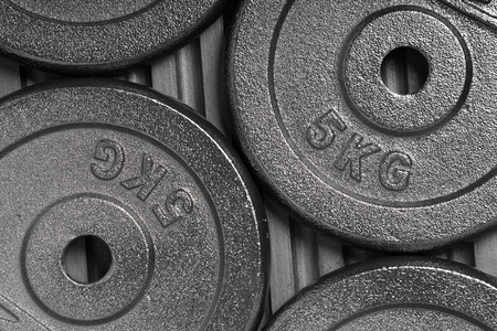 Weight plates on a black rubber floor inside a weight training gym  fitness studio Stock fotó