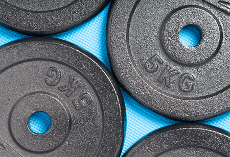 Weight plates on a colourful blue floor inside a weight training gym  fitness studio