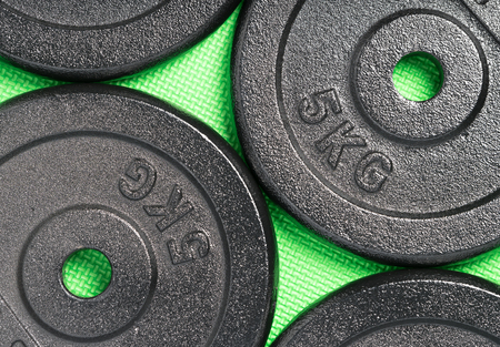 Weight plates on a colourful green floor inside a weight training gym  fitness studio
