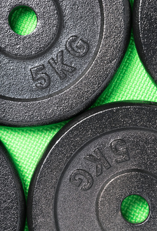 Weight plates on a green floor inside a weight training gym