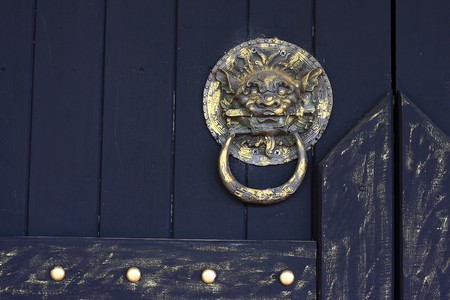 lionhead: Rustic lion-head knocker door, low-key  Stock Photo
