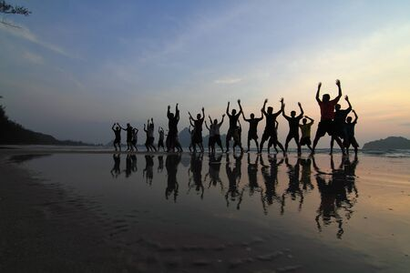 group of happy young people silhouettes jumping on the beach on beautiful summer sunset photo