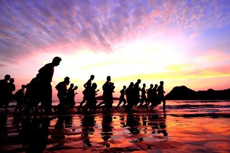 juventud: Grupo de j�venes se ejecuta en la playa Foto de archivo