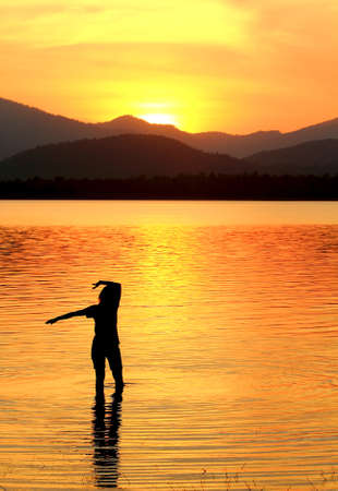 Silhouette of a girl in the water at sunset photo
