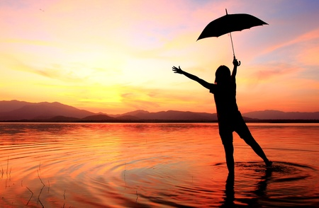 silhouette of young woman against summer sunset Stock Photo