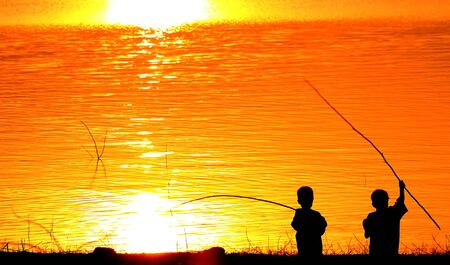 Silhouettes of two children playing along the river photo