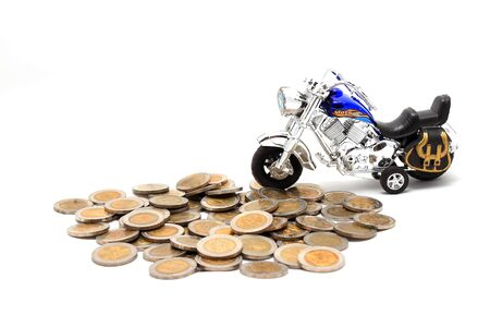 Motorcycle over a lot of golden coins (isolated on white) Stock Photo - 8545910