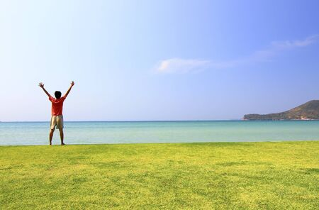happy man on the meadow against the sea landscape photo