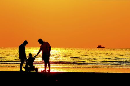 apoyo familiar: Imagen de la silueta de ni�o de padre por la orilla del mar, puesta de sol