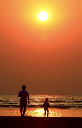 Silhouette image of father  child by the sea shore, sunset photo