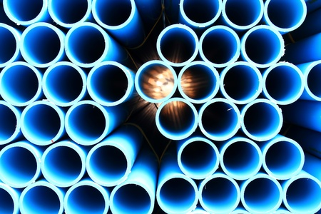 on end: blue pipes stacked in construction site, pattern closeup Stock Photo