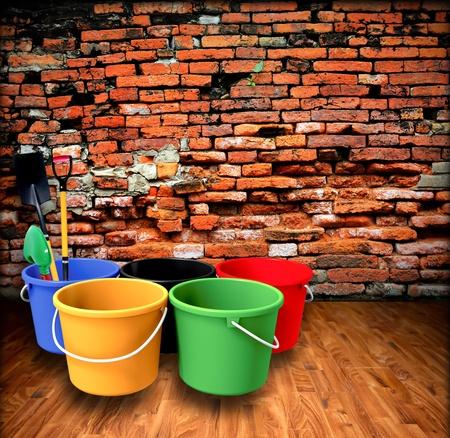 Bucket and shovel with a brick wall. photo