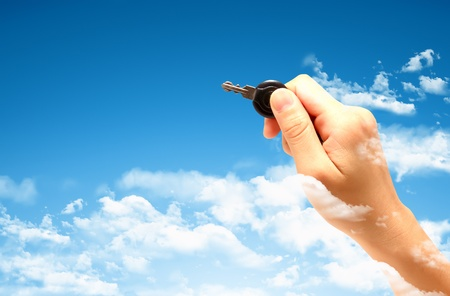 Woman's hand holding key with pretty sky background Stock Photo - 9132060