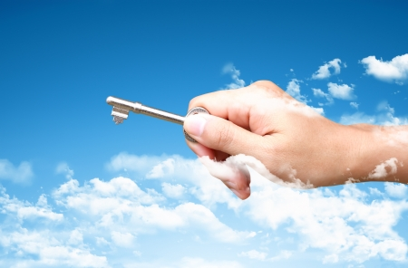Womans hand holding key with pretty sky background photo