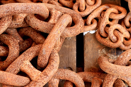 Old rusty chain on wooden background photo