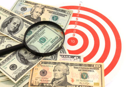 Money dollars and magnifying glass on   darts target Stock Photo - 9606229