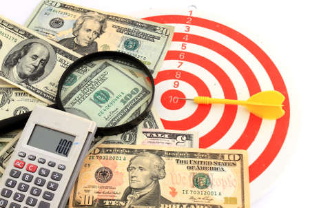 Money dollars and magnifying glass on   darts target photo