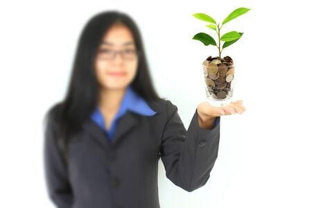 pretty young businesswoman holding a growing plant and coins (Select Focus) photo