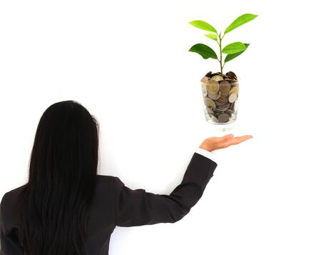 pretty young businesswoman holding a growing plant and coins photo