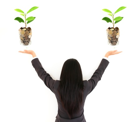 pretty young businesswoman holding a growing plant and coins Stock Photo - 9649974