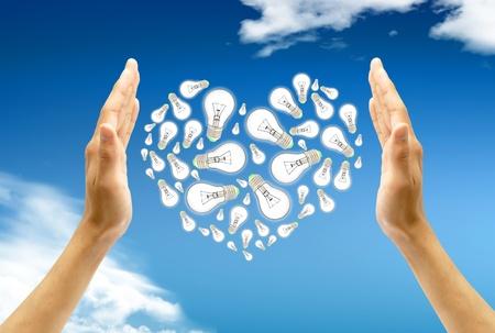 Ecological energy. Hand holds a light bulb against blue sky photo