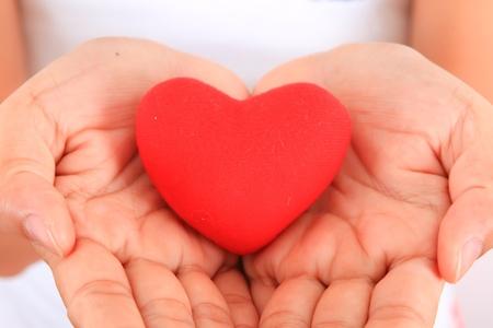 dando la mano: Manos de una mujer con el corazón rojo