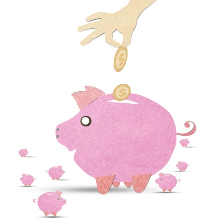Hand is inserting a coin into pink piggy bank with recycled paper stick photo