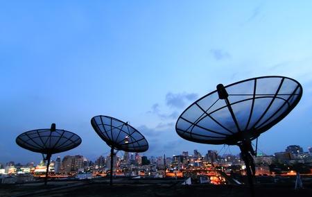telecoms: nero antenna antenna parabolica comunicazione su tramonto, cielo in cityscape