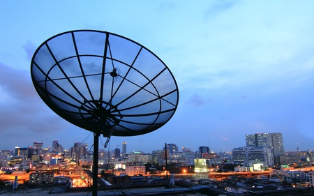 dish disk: black antenna communication satellite dish over sunset sky in cityscape