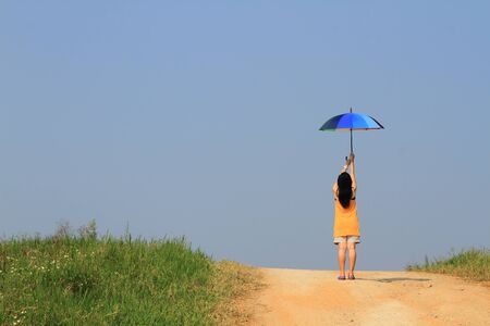 Beautiful woman holding multicolored umbrella and blue sky photo
