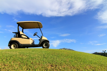 Golf cart on path, pretty green grass and blue sky background photo